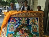 Dechen Tulku (center) with a thangka featuring Dorje Shugden as the central image and deity, surrounded by the five forms of Dorje Shugden, Vajrapani, Manjushri and Tsongkhapa with his two heart sons (Khedrup Je and Gyaltsen Je)
