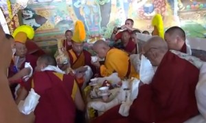 Lama Zopa accepting a tea offering from the worldly deity Gyalchen Karma Trinley at Sera Je Monastery