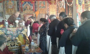 Khen Rinpoche receiving offerings from a long line of devotees during the puja