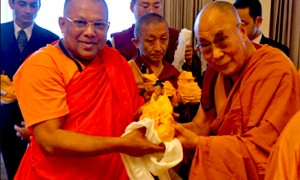His Holiness the Dalai Lama presenting a member of delegation of senior Sri Lankan monks with a Buddha statue after their meeting in New Delhi, India on March 19, 2015