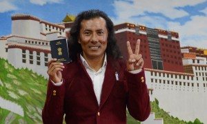Lobsang Wangyal proudly brandishes his Indian passport, which will allow him to vote in the upcoming Indian elections.