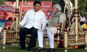 Chinese President Xi Jinping sits on a swing with Indian Prime Minister Narendra Modi at a riverside park in Gujarat